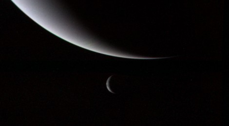 The crescent glow of Neptune and Triton taken by Voyager 2 as it heads to the edge of the Solar System